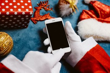 Smart Santa Claus working using smartphone on busy table surface background
