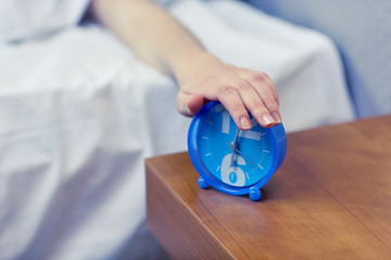 close up of hand on alarm clock in bedroom