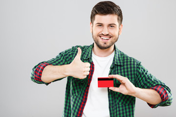 Man holding credit card and showing thumbs up