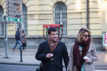 Young couple with coffee to go in hands crossing urban street.