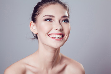 Smiling brunette girl with beautiful makeup on grey background, youth and skin care concept.