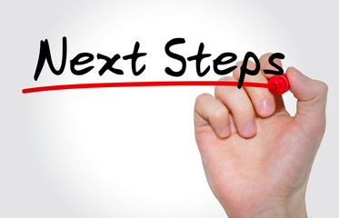 "Hand writing inscription ""Next Steps"" with marker, concept"