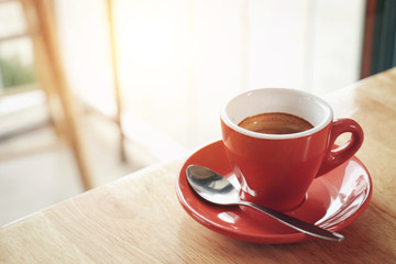 Red cup of espresso on wooden table in coffee cafe. selective focus. Vintage tone.
