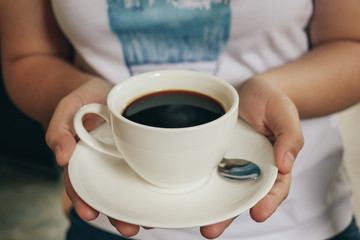 women hold a cup of Black coffee. Vintage tone. Selective Focus.