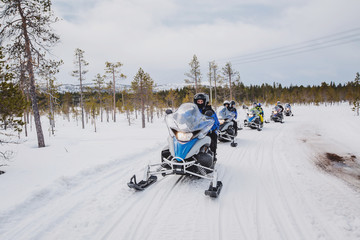 man driving snowmobile in Finnish Lapland