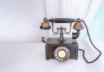 Ancient phone is placed on a wooden table, vintage style.