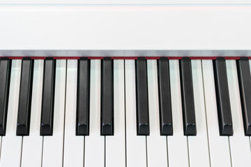 Classical piano with red decorative strip at the base of keys, close-up