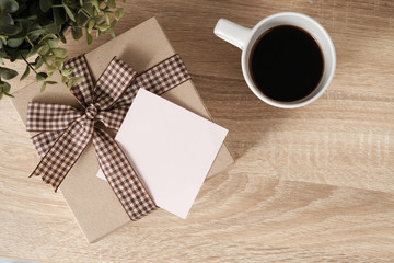 Gift box on wooden table with blank paper for text and coffee