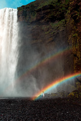 Woman standing underneath rainbow and waterfall