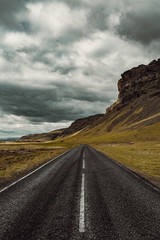 View of empty road by mountain against cloudy sky