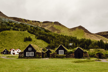 Grass roofed cottages by hills