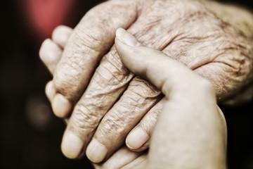 Hand einer Seniorin wird von der Hand einer jungen Frau gehalten