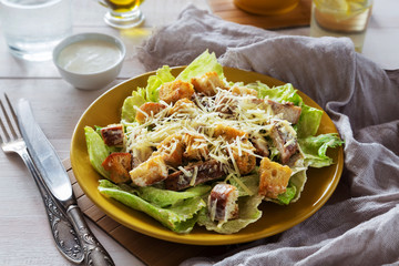 Mixed Caesar Salad with chicken on a yellow plate