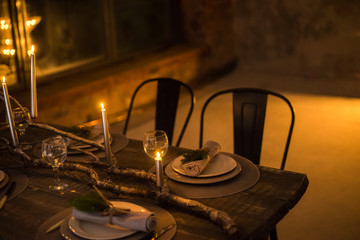 Festive dinner by candlelight. Wooden table with decoration