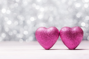 Two pink Valentines hearts over white abstract lights