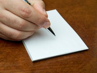 Closeup hand writing blank memo book