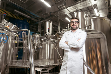 Joyful man posing with brewing mechanisms