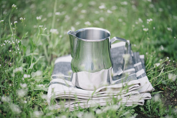 Frothing milk pitcher on the cloth napkin outdoors on the green grass background