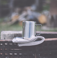 Frothing milk pitcher on the cloth napkin on the old red bricks