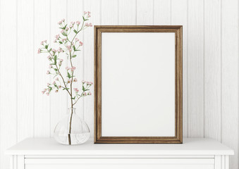 Vertical interior mock up with empty wooden frame and blooming twig on wooden wall background. 3D rendering.