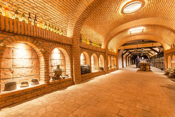 Brick walls of old wine cellar Khareba Winery with many bottles in underground cool room