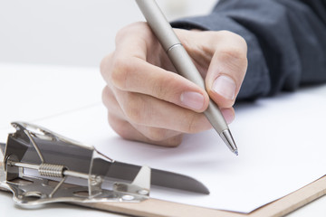 closeup of hands with the pen writing or signing