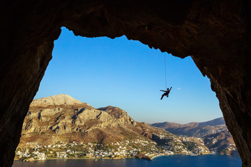 Silhouette of a rock climber hanging on rope while climbing in cave, Telendos Island, Greece