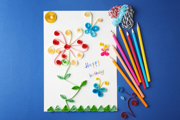 Handmade gift card and colorful crayons on blue background