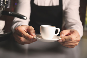 Male barista holding cup of coffee at table