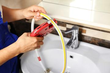 Plumber fixing water flexible hose in bathroom
