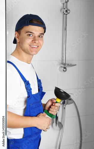 young handsome plumber with plunger in bathroom indoors stockfotos und lizenzfreie bilder auf. Black Bedroom Furniture Sets. Home Design Ideas