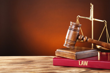 Judge gavel, scales and book on wooden table
