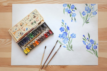 Set of watercolors, brushes and beautiful picture on wooden table