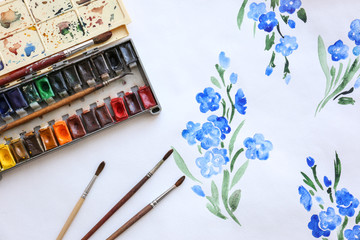 Set of watercolors and brushes on beautiful picture