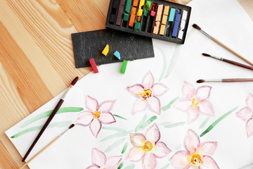 Crayons, brushes and beautiful picture on wooden table