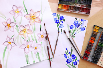 Set of watercolors, brushes and beautiful pictures on wooden table