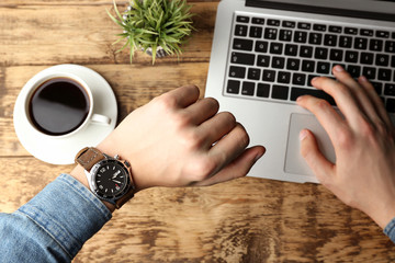 Hands of young man looking at watch while working with laptop