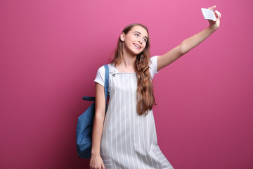 Pretty teenager girl taking selfie on color background