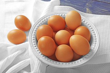 Plate with raw eggs on tablecloth