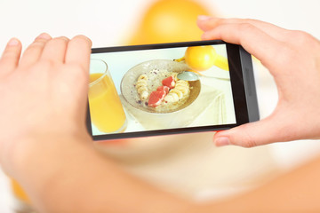 Female hands photographing food with mobile phone
