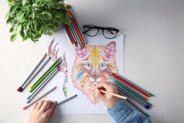 Young woman sitting at table with coloring pictures for adults, closeup