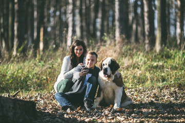 Young couple taking selfie photo with their Saint Bernard puppy.