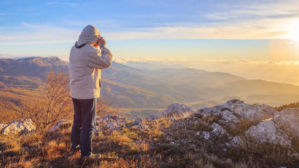 Traveller in sports wear stands on the top of autumnal mountains