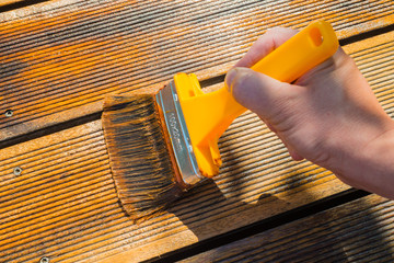 Oiling Terrace with Wide Brush - painting wooden patio deck with protective oil