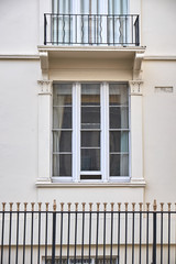 Window section with three narrow hung frames in building facade with a balcony just above