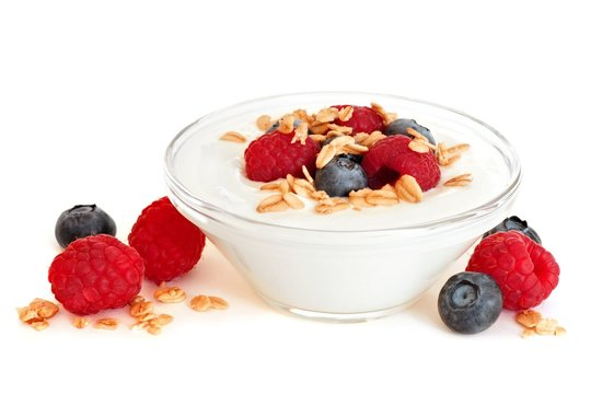 Clear bowl of yogurt with raspberries and blueberries over a white background