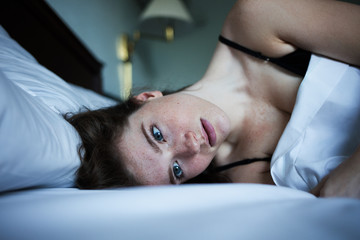 Portrait of pensive and sad woman in bed with green eyes
