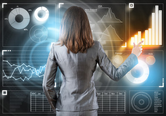 Businesswoman standing with back and pressing icon on media screen