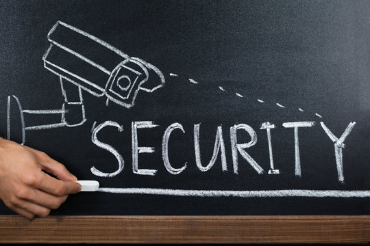 Person Hand Showing Security Concept On Blackboard