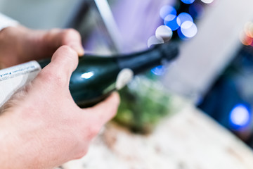 Man hands opening champagne bottle at party